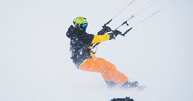 Osoba uprawia snowkite na zaśnieżonej równinie