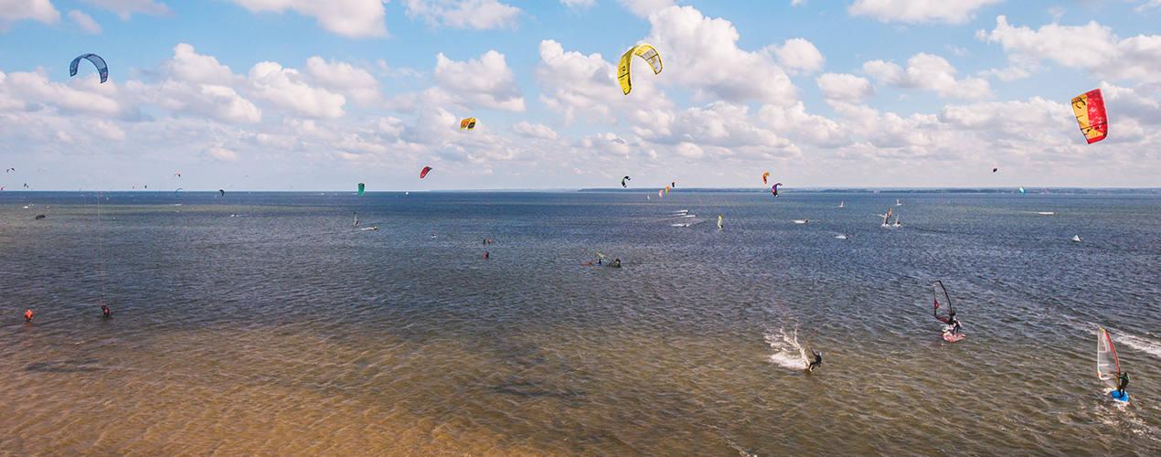 Kitesurferzy pływają na akwenie szkoleniowym szkoły kitesurfingu